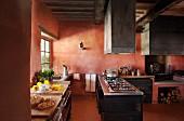 Moderne Einrichtung in einer mediterranen Küche mit ziegelroten Wänden