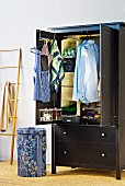 Clothing hanging in open, black wardrobe with drawers next to patterned waste-paper basket