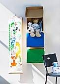 Soft toys in coloured boxes hung one above the other on the wall next to fabric height chart