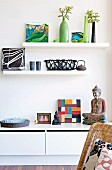 Buddha figurines, Oriental teapot and various objet on sideboard and shelves