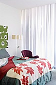 Bed with two-tone bedspread and lamp with stylised plant motif in corner of bedroom with large floral patterns