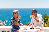 Couple breakfasting on a terrace with an ocean view