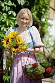 Woman with sun flowers and vegetable basket in front of a farmhouse