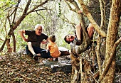Grandfather and grandsons playing in the forest