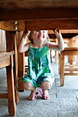 Little girl playing under a table