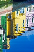 Historic homes in assorted colors reflected on the surface of the water in a canal