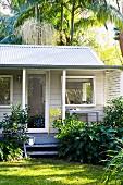 Weisses Gartenhäuschen mit Veranda unter Palmen