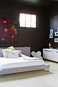 Modern double bed against black-painted wall with floral painting next to transom window in corner of room