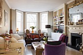 Pleasant, English living room with bay window, open fireplace, group of sofas and armchairs and coffee table