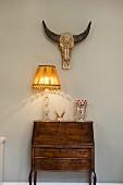 Table lamp on Baroque bureau against painted wall below animal skull