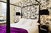 Black four-poster bed against black and white floral wallpaper and flanked by tall bedside lamps on black-lacquered beside tables