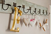 Gold, wooden letter ornament and scented sachets hanging on peg rack