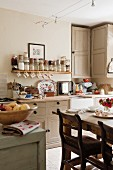 Dining area in front of kitchen counter below open spice shelf in English country-house kitchen