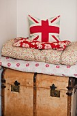 Cushion with Union Flag motif on stack of blankets on wooden trunk