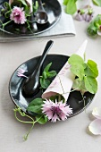 Table setting with a paper cone with a signature filled with corn flowers and trailing vetch