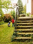 Old stone steps in the garden, children playing next to it