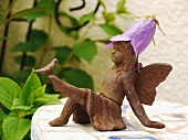 Small angel figurine with a flower hat in the gardne
