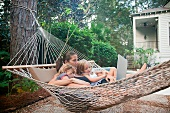 Mother and daughters on hammock with laptop