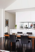 Wooden dining table and black chairs in front of white fitted kitchen with sink unit