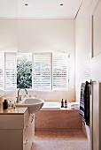 Base unit with protruding washbasin and fitted bathtub below windows with louver blinds in narrow bathroom