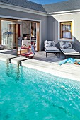 Pool and loungers on a terrace in front of an open glass, sliding door with a view into the living room
