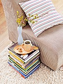 Mug of tea and vase of flowers on stack of books on floor next to armchair with beige corduroy cover and striped cushion