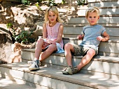 Brother and sister sitting on wooden steps, portrait