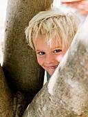 Boy peeking from behing tree, portrait