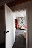 Blick in ein Wohnzimmer mit Natursteinwand und Steinfliesen