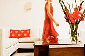 Wohnzimmertisch mit roten Gladiolen, dahinter Frau im roten Kleid vor weißem Sofa