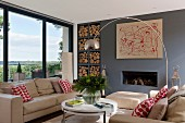 Beige sofa set and designer lamp above coffee table in front of fireplace in wall painted blue-grey; shelves of firewood