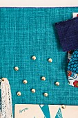 Drawing pins and fabric swatches pinned on turquoise linen fabric