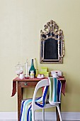 Striped towel on back of chair in front of antique console table below mirror with ornate metal frame on pastel green wall