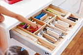 Open cutlery drawer with various cutlery in wooden insert and child's hand reaching for child's cutlery