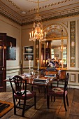 Lit candles in chandelier above dining table and upholstered chairs; custom-made replica mirror surrounded by gilt wall panelling in background