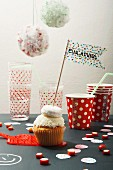 Cupcake with washi tape flag, paper cups, glasses and party decorations