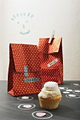 Party loot bags with name tags and one cupcake