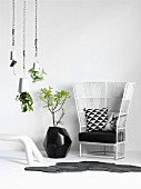 White wicker chair with black cushions, black floor vase against wall and decorative planters hanging from ceiling