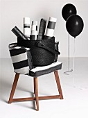 Rolls of paper in basket on chair with wooden frame and black and white cover next to black balloons on metal frames