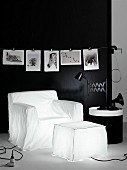 Armchair-shaped and pouffe-shaped lamps below black and white animal photos on black wall