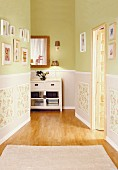 Gallery of pictures on walls painted lime green above panelled dado area in bright hallway