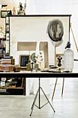 Moderne Arbeitsplatte mit allerlei Vintage Deko-Objekten vor aufgestellter Leinwand