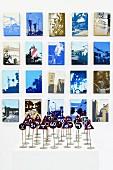 Vintage Miniatur Verkehrsschilder auf weisser Ablage vor künstlerisch verfremdeten Photos an Wand