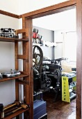 Shelves of machine components in foyer next to open door with view of vintage machinery beyond