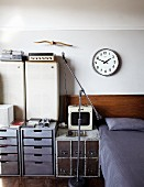 Stereo equipment on drawer cabinets in various styles next to bed with headboard below clock on wall