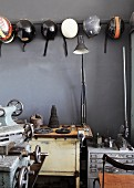 Collection of motorbike helmets hanging on grey wall and vintage machines in cellar room
