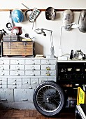 Motorbike wheel in front of vintage chest of drawers and sheet metal components hanging on wall