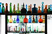 Pretty coloured glass bottles and vases on partition shelving