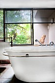 Free-standing retro bathtub with towel rail in front of window with half-closed blinds and view of garden