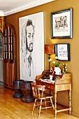 Kleiner Sekretär mit Holzstuhl neben grossformatigem Bild an ockerfarbener Wand im Flurbereich